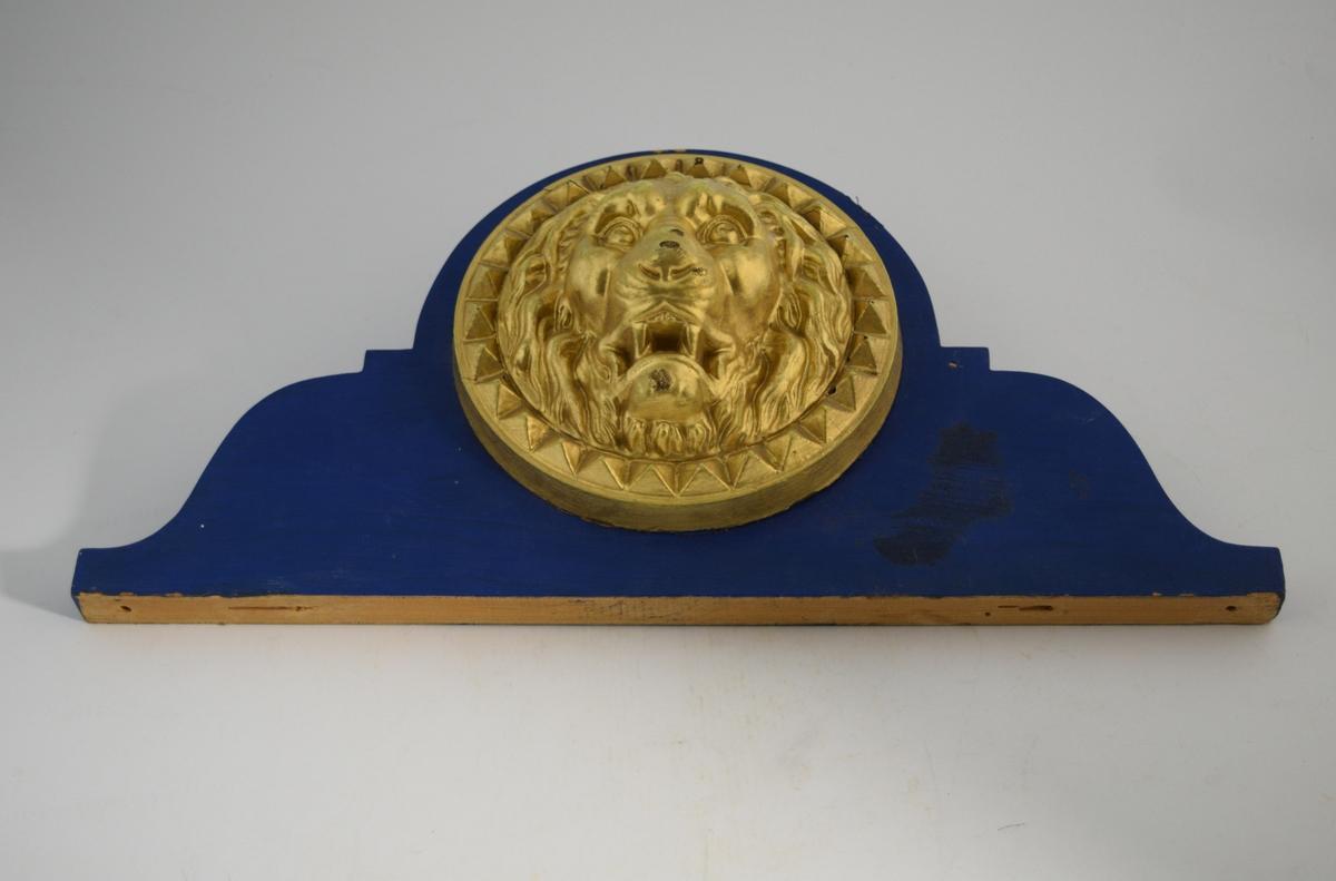Figur som forestiller et løvehode, dekket i gull. Festet på en bakplate i tre. Bakplaten er malt svart.
