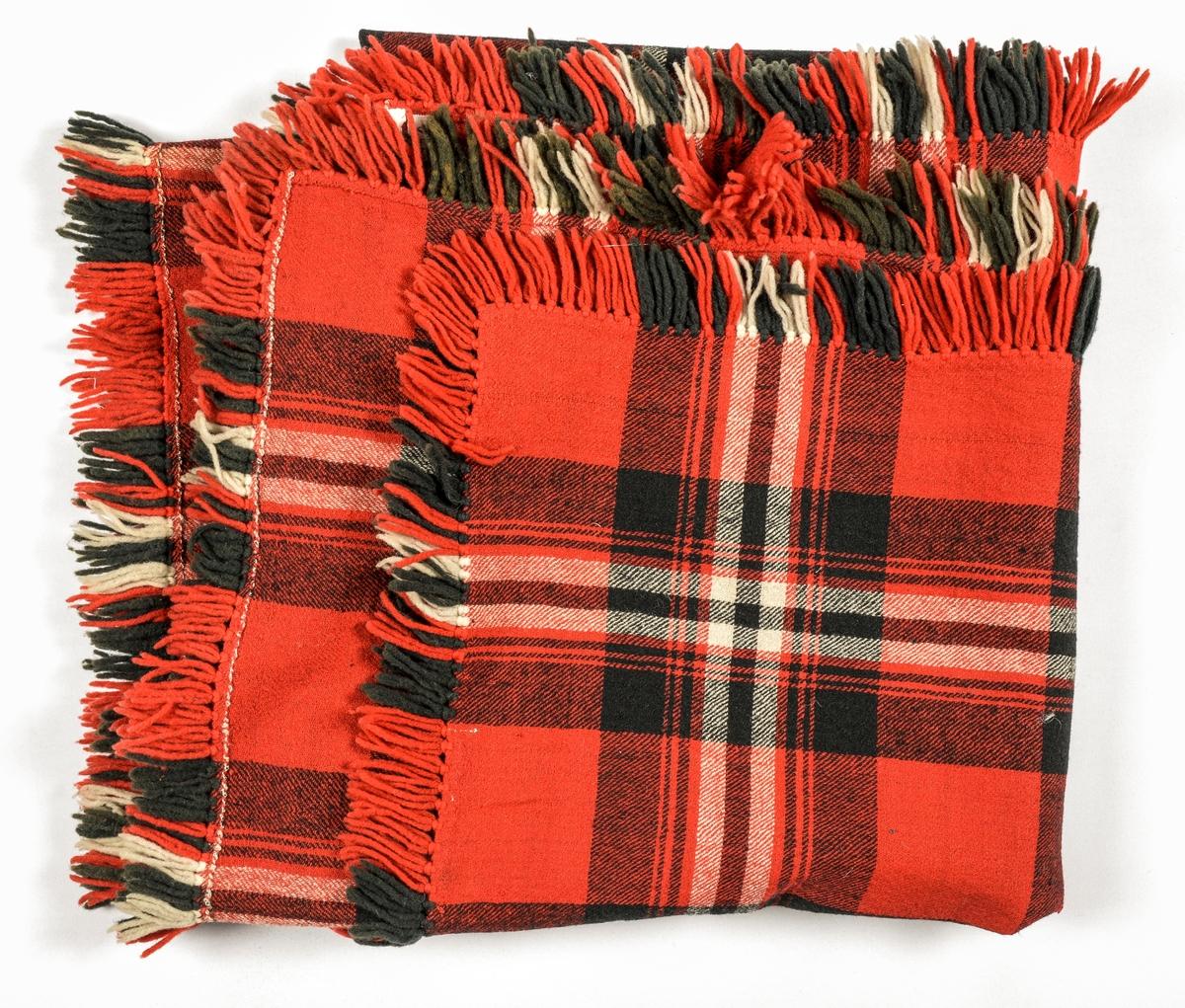 Sjal i ruta raudt, sauesvart og kvitt ullgarn. Kypertvove. Samansydd på midten, falda rundt alle sidene og påsette frynser av laustvinna ullgarn i same farger som sjalet.