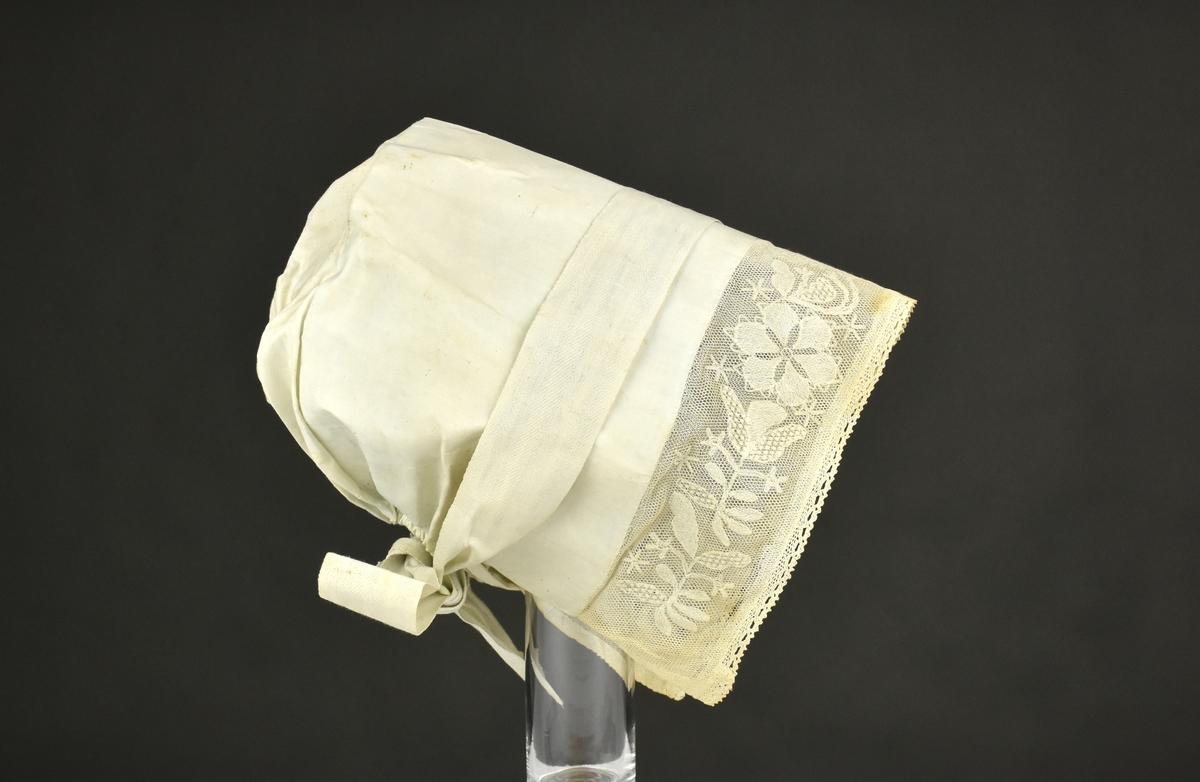 Huvudbonad av linne med framremsa av broderad tyll, kantad med smal och knypplad spets.