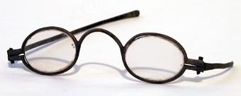 Glasögon med bågar av mässing och ovala glas.