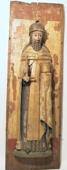 Manligt helgon gjort av ljust lövträ. Figuren håller ett svärd i högra handen samt ett förgyllt kärl och manteln i vänstra och står mot ett skåp vars ryggstycke är gjort av furu. Skåpets sockel, baldakin och sidostycken saknas, hål för dymlingar till fäste av dessa finns runt alla kanter. Svärdets skida saknas. Bemålningen är välbevarad. Skåpets ryggstycke är glansförgyllt, glorian är inristade linjer gjorda med passare, mellan linjerna finns punserade rosetter. Nedtill klar röd färg, cinnober, upptill brunrött. Helgonets mantel är glansförgylld. Klädnad och huvudbonad i imitationsförgyllning, gul lasering på silverblad. Hår och skägg är grå. Svärdfästet är rött, backen grön.