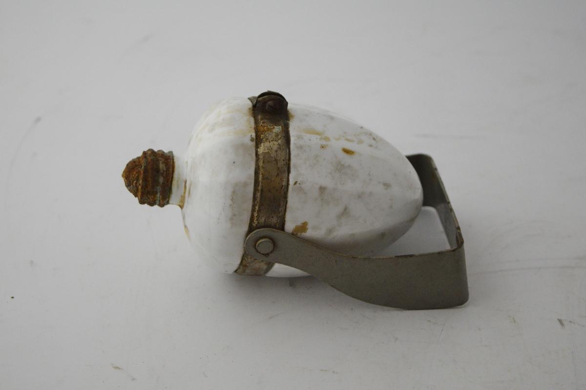 Fasetter/ eikenøttformet beholder for såpe med stativ til å feste beholderen til veggen. Metallring rundt porselensbeholderen er festet til veggstativet. Beholderen snus når såpen skal brukes.