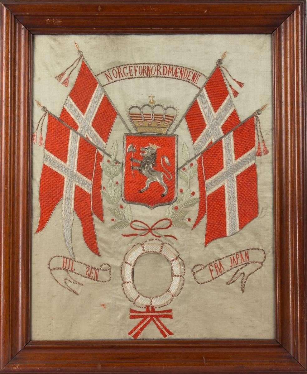 Brodert silkebilde med tekst NORGE FOR NORDMÆNDENE. Midt i motivet norsk riksvåpen med krone omkranset av to norske flagg på hver side. Under brodert livbøye med plass til fotografi/portrett uten at det har vært montert noe bilde.