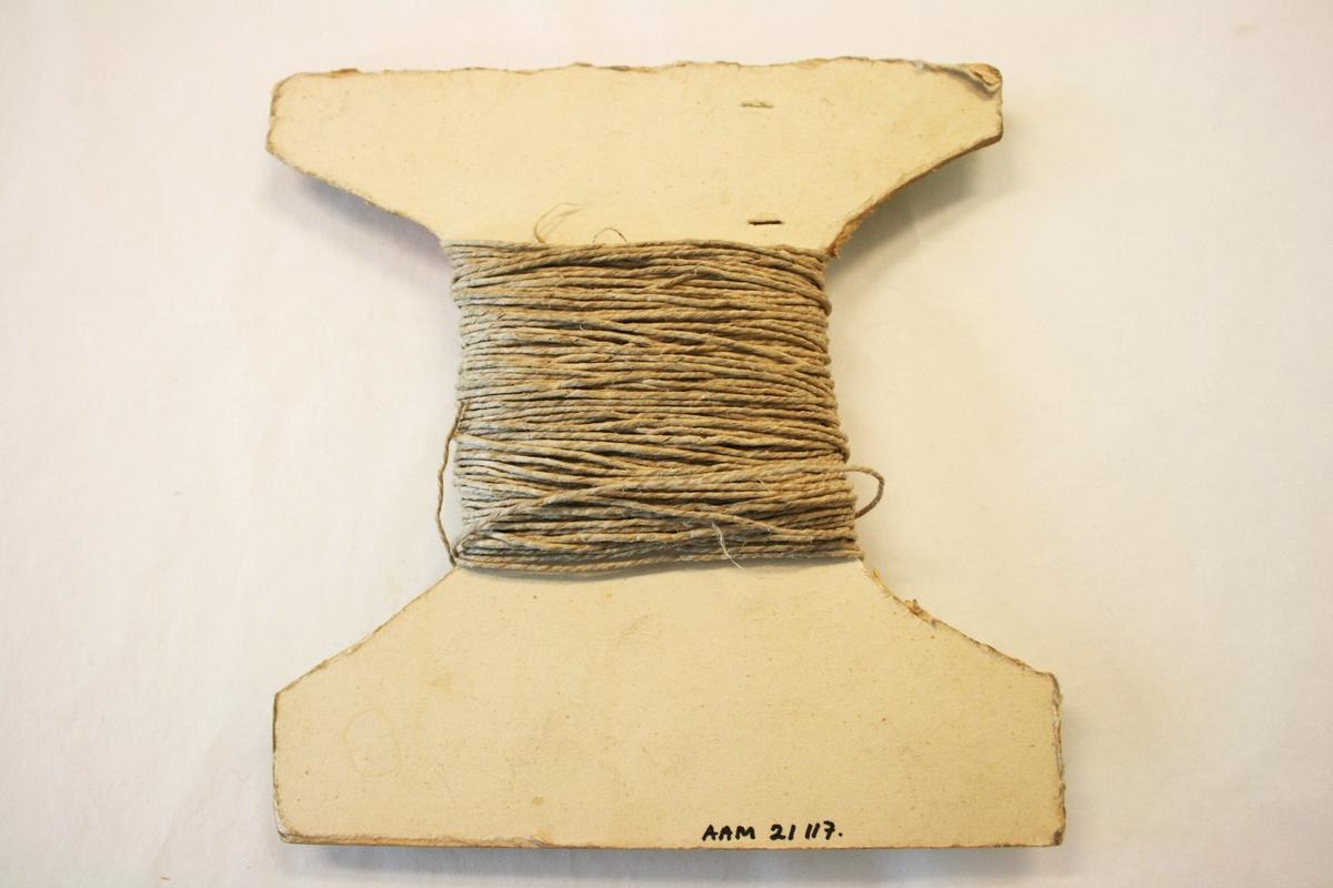 Hyssingen er viklet rundt et omriss av en trådsnelle i papp.