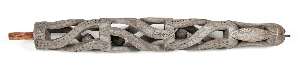 Rockhuvud av trä, gråmålat, utskuret, geometriska mönster, med tre rörliga kulor inuti.