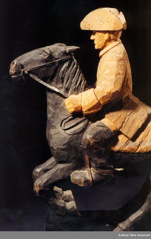 KLM 39255:31. Skulptur, av trä, bemålad. Ryttare till häst, Karl XII. Figur stiftad mot träplattan. Ryttaren har uniformsrock och hatt av karolinermodell samt bär sporrar. Hästen är utrustad med träns och betsel i svartmålad plåt, smidda stigbyglar i koppar samt randmålad sadel i blått och bronsfärg(?). Signerad, H.C. På hästens ländrygg samt på plattans ovansida. Inristad kursiverad text på plattans långsidesfront, E. Tegners tex: Högbarmad, smärt, gullhårig, en ny Aurora kom, Från Kämpe tjugoårig hon vände ohörd om. Datering, omkring 1930. Tillverkad av Helge Rugland, f. Carlsson. Figuren hör samman med KLM 39255:17 Aurora Königsmarck, vilka utgör en figurgrupp, benämnd, Karl XII och Aurora Königsmarck.