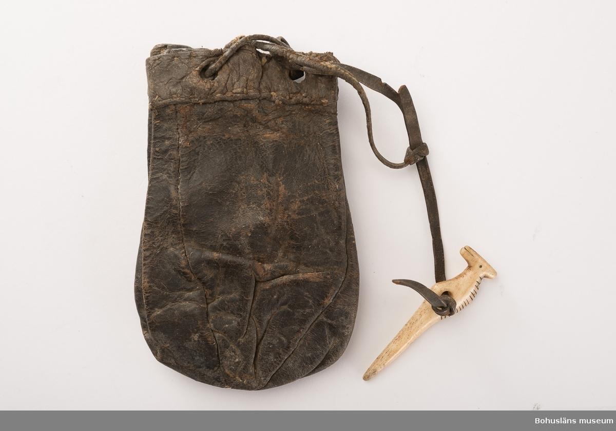 En skinnrem håller samman påsen, i remmen sitter en piprensare av ben fästad. Piprensaren har formen av ett djur; graverade linjer på ryggdelen, samt som mun och öga. Pungen är tillplattad och mycket stel (juni 2007).  Ur handskrivna katalogen 1957-1958: Tobakspung + piprensare. L. 12,5. Tobakspung av läder. Piprensare av ben. Föremålen hela.