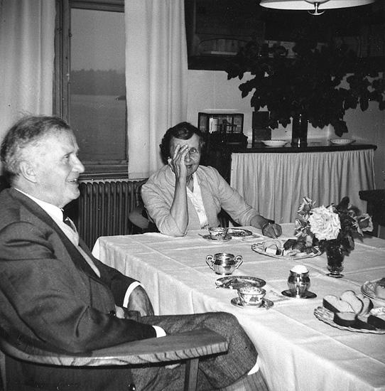 "Enligt uppgift: ""Hans Pettersson med fru Dagmar på kaffe hos Åkermo´s. Fotografiet taget i biblioteket, 1960-talet""."