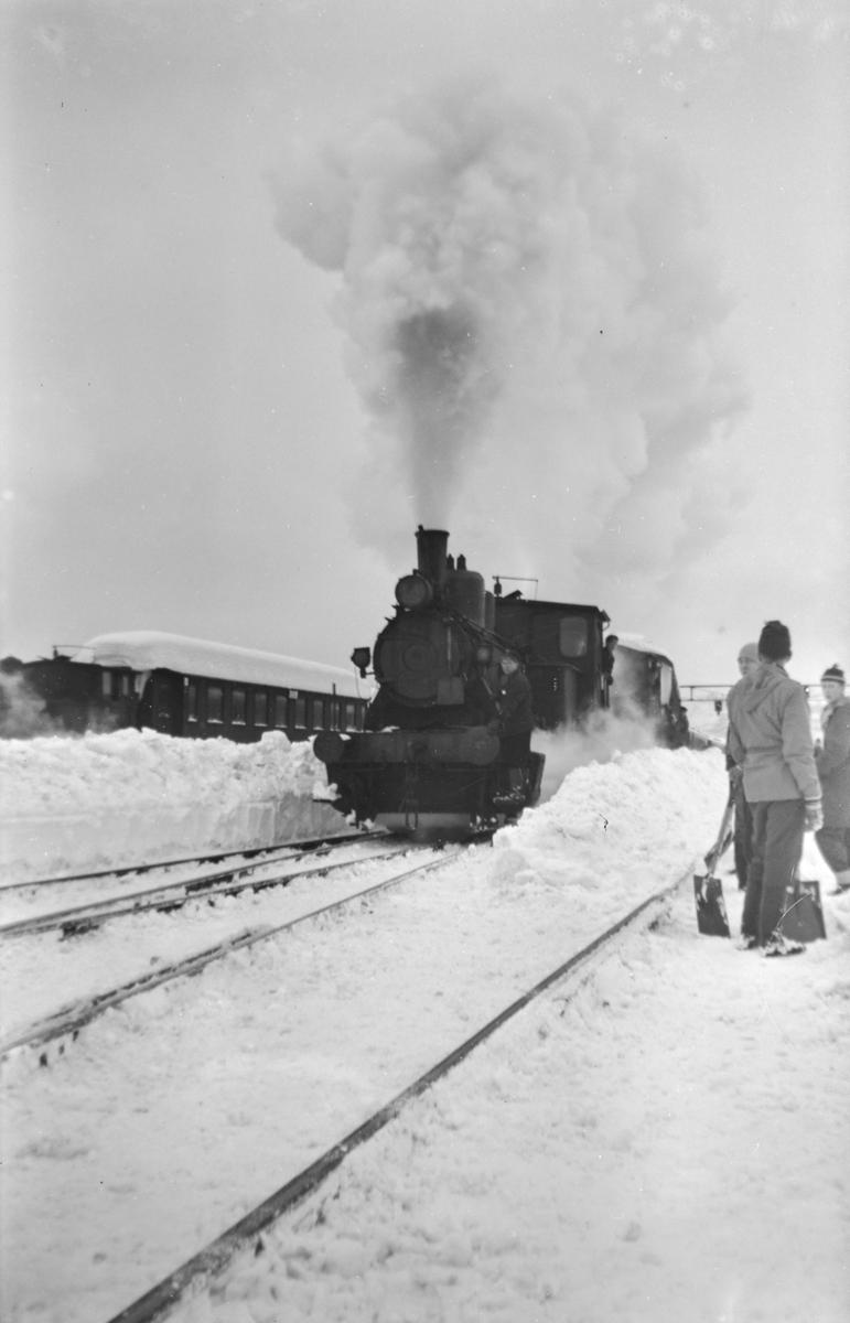 Snøryddingsmannskaper og snøryddingstog trukket av damplokomotiv type 25a på Trondheim stasjon.