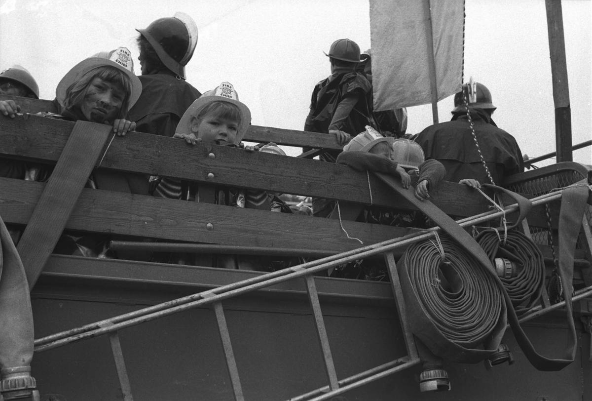 """Unger kledt ut som brannmenn, fotografert bakpå en lastebil på """"Barnas Dag""""."""