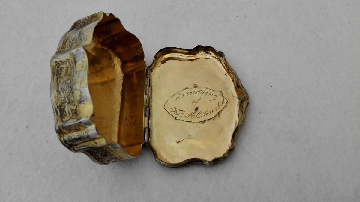 Utvendig sisellert og forgyldt. Har billeteframstillingar på loket og i botnen. Under loket er det pålodda ei forgyldt sølvplate med inskriptsjon.