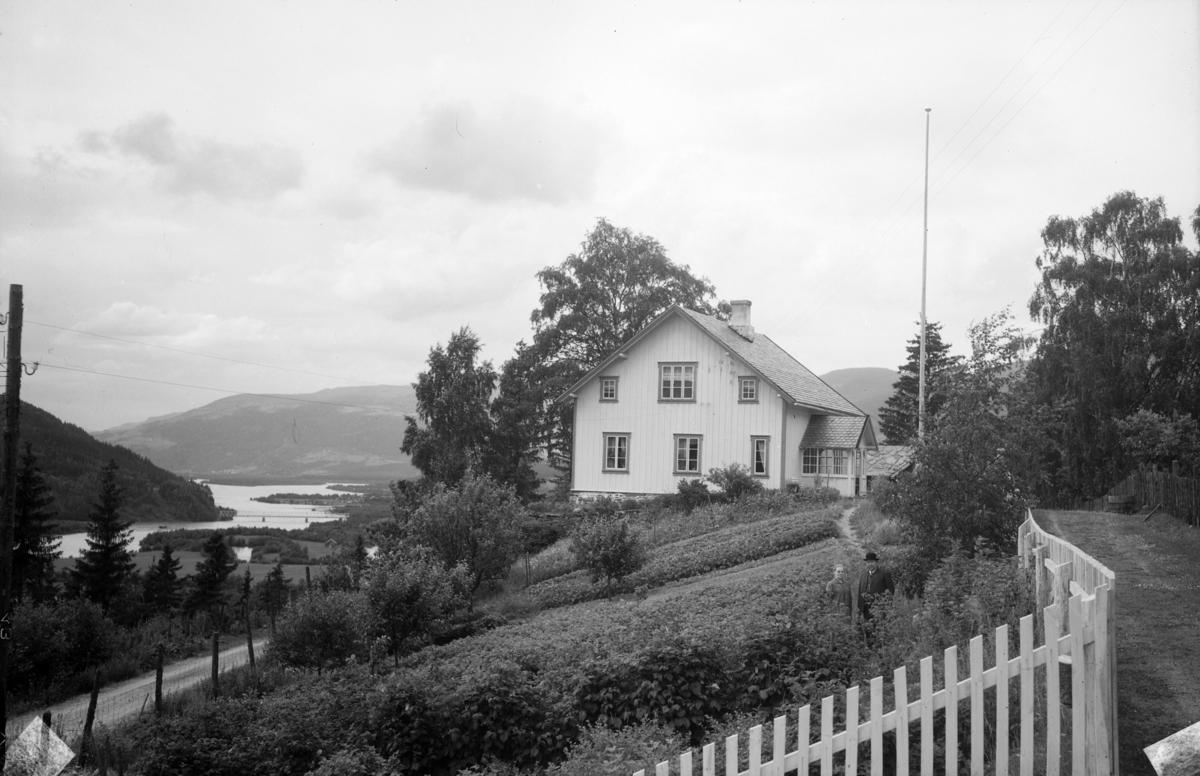 Ringebu, Vekkom. Boligen 'Solvang' nedenfor Ringebu prestegård. I hagen står lærer Hans Nyhus f i Lom i 1860, død 1936 og hans kone Ingeborg. Vegen på oversiden og i bakgrunnen Gudbrandsdalslågen med jernbanebrua.