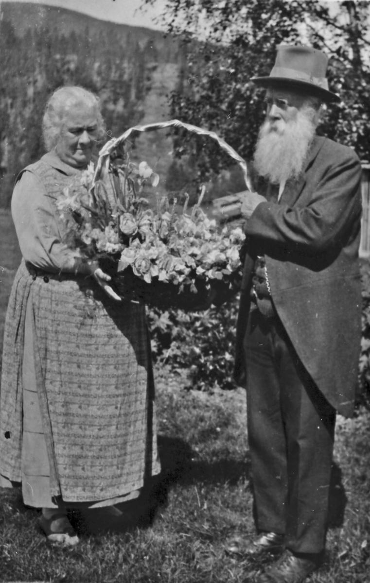 Karen og Ivar Mortenson Egnund med en stor blomsterkurv.
