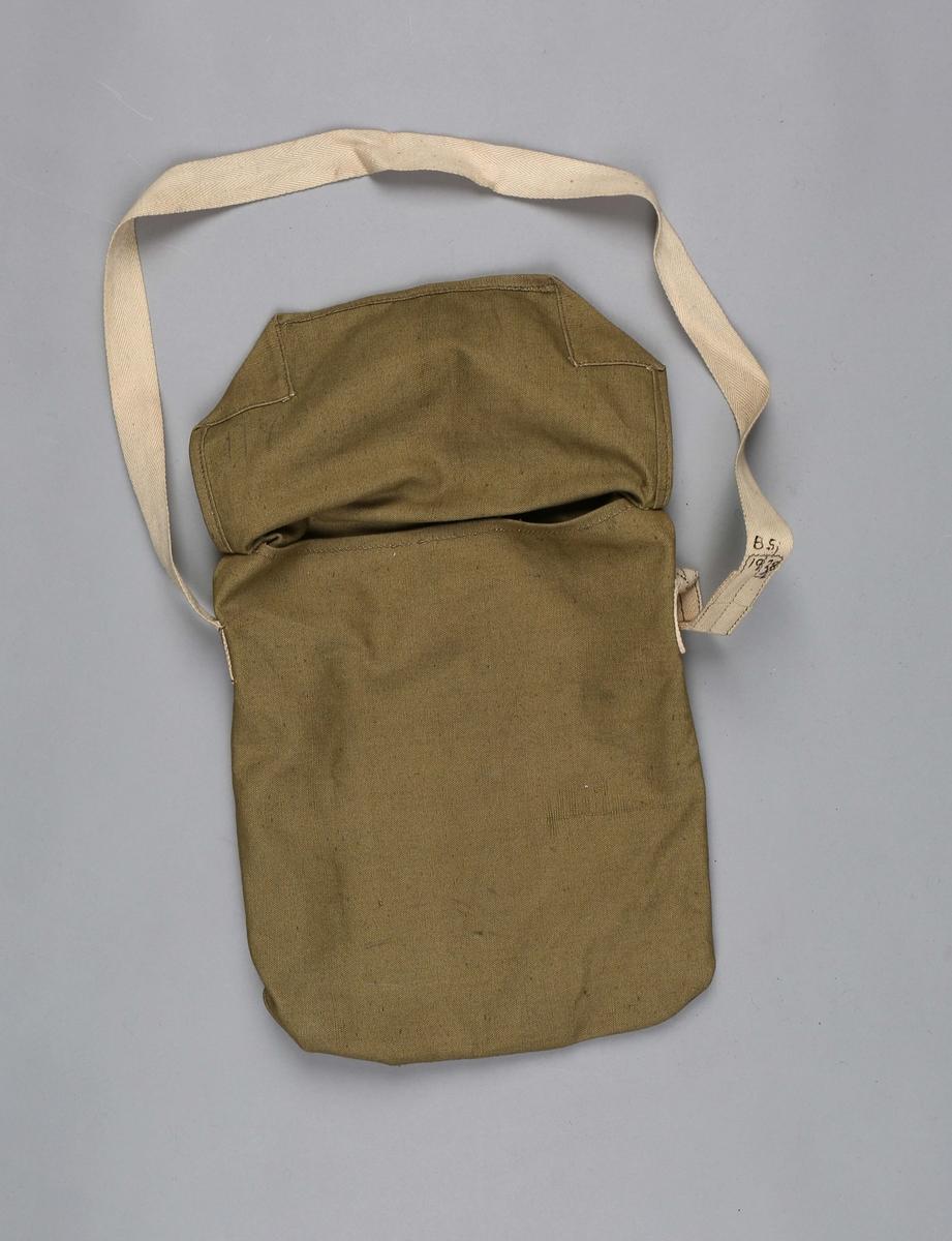Gassmaske i tøyveske. Tøyveske med lokk og skulderreim som masken oppbevares i når den ikke er i bruk.