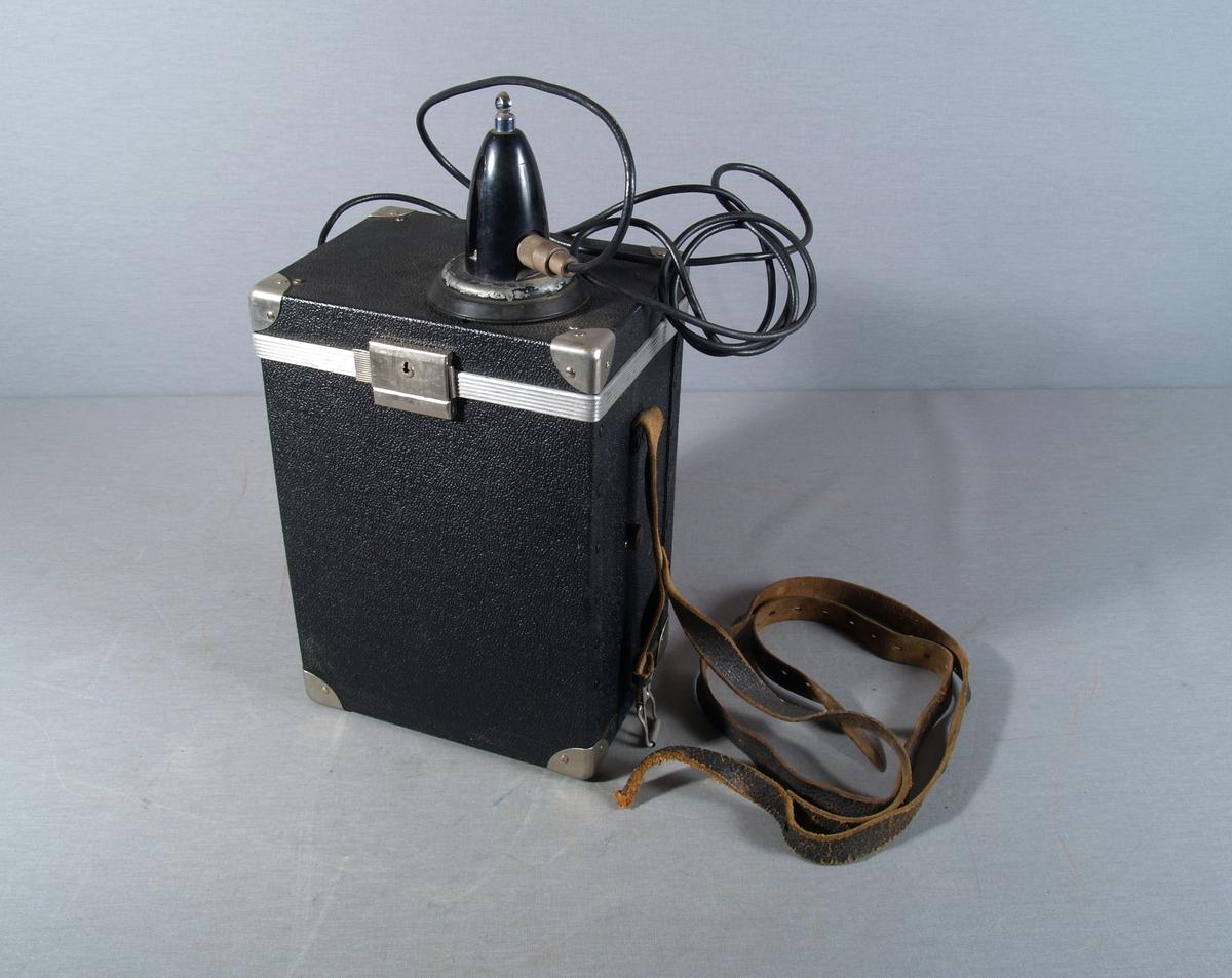 Bærbar radiotelefon med mikrofon i kasse med bærereim. Antennekabel (coax) ut gjennom kassens side og til antennebase/sokkel festet på kassens lokk.  Selve antennen mangler. Kassen har låsbart lokk.