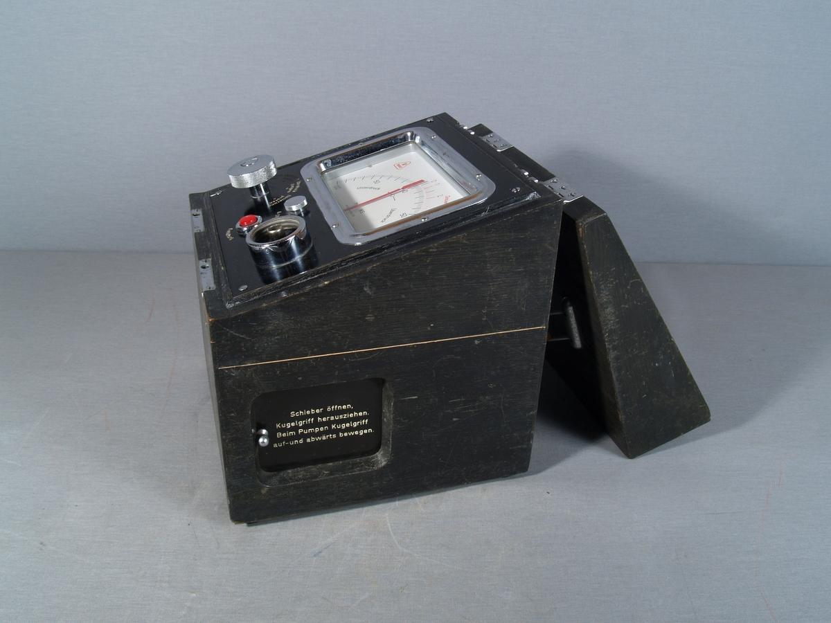 """Testapparat for røykdykkerutstyr. Apparatet er montert i en trekasse med henglset lokk og håndtak på toppen. To låser i front. Innvendig skråstilt panel som består av en måleskala med viser som viser over- eller undertrykk, mm WS, skalaen går fra 0 til 100 på begge sider. I tillegg er det en skala, dosering l/min. fra 1-4. Under skalaen en velger for """"Unterdruck pumpen"""", """"Dichtigkeit prüfen"""", """"Überdruck pumpen"""" og """"Dosierung prüfen"""". En knapp for nullstilling av viser på skalaen, en trykknapp for """"Entlüftung"""" og et påkoblingspunkt for testobjekt. På kassens høyre side et skyvelokk foran et rom i kassen, med slange og manuell pumpe med kulegrep. I lokket skilt med bruksanvisning for apparatet. I lokket finnes også to festeklemmer i metall."""