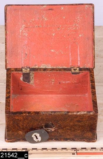 """Anmärkningar: Schatull, Jacob Sjölin, 1767-1779.  Gångjärnsförsett rektangulärt lock med rundade kanter. Undertill försett med """"KÖPINGS HALLSTÄMPEL"""" samt """"JAC. SIÖLIN. / KÖPING. No 180."""" (bild 21542__b). På fronten finns en senare nyckelskylt i metall och pärlemor. Invändigt klätt med marmorerat papper, nu sekundärt målat med röd färg (bild 21542__c). Fyra konturerade fötter. H:95 Br:195 Dj:140  Hela schatullet är fanerat med alrot, blindträet är av furu. Under nyckelskylten har schatullet en relativt stor skada i form av ett hål. Den mörka infärgningen i alroten är fortfarande i tämligen bra skick. Mälardalen och framför allt städerna Arboga, Köping, Kungsör och Eskilstuna var under 1700-talets senare hälft och början av 1800-talet centrum för tillverkning av alrotsfanerade möbler och föremål. Här tillverkades bl.a. fällbord, byråar och olika sorters askar. Föremålen såldes inte bara inom mälardalen utan även till Stockholm och till andra länder. Det främsta namnet inom alrotsföremålsproduktionen är Jacob Sjölin (1737-1785). Alroten togs inte från alens rötter utan från stamansvällningar vid rötterna. I synnerhet vid Mälarens stränder har tillgången på detta sorts virke varit god. På slottet förvaras en kortkatalog, upprättad av f.d. antikvarie Carin Thorsén. Den upptar över 300 alrotsföremål tillhörande museer, privatpersoner etc.  Jacob Sjölin (1737-1785), gick i lära hos Jonas Nordling i Arboga. Sjölin blev mästare under hallrätten i Köping och Kungsör 1767 och kvarstod som mästare intill sin död 1785. Ungefär 2000 föremål tillverkades i hans verkstad. Sjölins speciella ytbehandling (fernissa) på möblerna gav dem en särskild glans och hållfasthet. Ingen mästare i Sverige har överträffat Sjölin i framställandet av alrotsfanerade möbler. Sjölin använde sig av tre olika brännstämplar, av Åke Nisbeth klassificerade som typ A, vilken är äldst men också använd under hela Sjölins livstid och även efter hans död, mellan 1785-1788 då verkstaden drevs av Sjölins änka. Typ"""