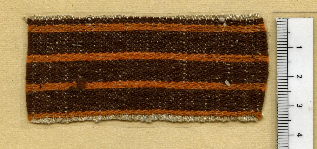 Anmärkningar: Vävprov av halvlinne i tuskaft. Varpen är av lin. Inslaget av bomull är randat i brunt och orange.