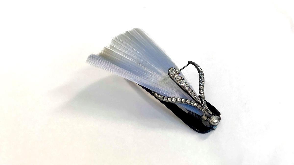 Pyntekam, ca. 1920. Form: Tre lange tinder. I overkanten er festet similismykke i form av tre  fjær besatt med med diamanter, og bak dem en hårvifte av lyst blå hår.
