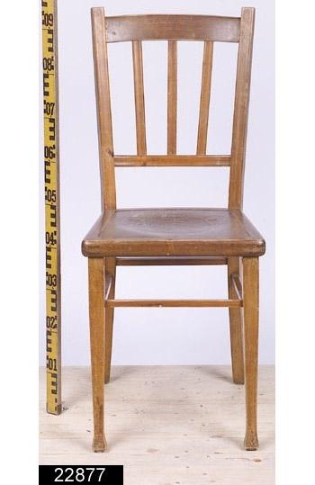 """Anmärkningar: Stol, jugend, omkring 1910.  Svagt konvext överstycke. Svängda bakstolpar (jämför bild 22879__b). Genombruten rygg med tre ryggspjälor som är fästa på en ryggslå. Sits av trä med pressat stilblandat mönster i form av bl.a. slingrande ornament och en fruktskål i mitten och två mytologiska figurer på flankerna (jämför bild 22879__c). Raka framben med fyrkantiga svagt pyramidformade fotavslutningar. Under fotavslutningarna finns runda fotstöd i gummi. Fyra benslåar binder samman benen, dessa sitter i olika höjder. H:930 Br:395 Dj:495  Hela stolen är betsad. Observera att bilderna är attribuerade till den identiska stolen med inventarienumret 22879.  Historik: I kortkatalogen står följande (Hämtat från invnr. 22876): """"Inköpta i samband med utställningen """" Bostad """" hösten 1985 från Britta Strandberg, Svartbäcksg. 94a, Uppsala. Ursprungligen inköpta i Lewin Johanssons Möbleringsmagasin i Västerås 1916 av montör Axel Johanzon, Hammarbygatan 2 i Västerås och hans hustru Tekla till deras första hem, som strax därefter flyttades till lantvärnsgatan 14 i Västerås. Köpet omfattade 4 stolar för kronor 24 och var en del av det hela möblemang som inköptes vid samma tillfälle omfattande toalettbyrå, matbord, 4 stolar, soffa, fällbord, soffa, portierer och rullgardiner. Summan kr 315: 30 betalades genom avbetalningar på två år."""""""