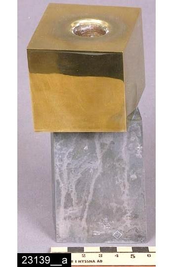 """Anmärkningar: Ljusstake, 1967.  Ljusstake i två delar med romboidliknande former. Överdelen är av mässing och underdelen är av förtennt mässing. På sidan finns stämplarna """"SKULTUNA 1607 F 7"""" (bild 23139__b), F står för Pierre Forssell (formgivare på Skultuna 1955-1986). Tidsangivelsen grundar sig på en tidigare registrering av f.d. antikvarie Monica Looström 1988. Observera att ljusstaken är inköpt direkt från formgivaren. Enligt en broschyr, utgiven av museet 2007 och benämnd """"Skultunastämplar 1800-2000"""", började den typ av stämpel som finns på föremålet användas 1922. Den användes fortfarande år 2007. H:135 Br:60  Tillstånd: Nyskick.  Historik: Inköpt från Pierre Forssell, Mjölnarvägen 1, Skultuna, för 1200 kronor 1988."""