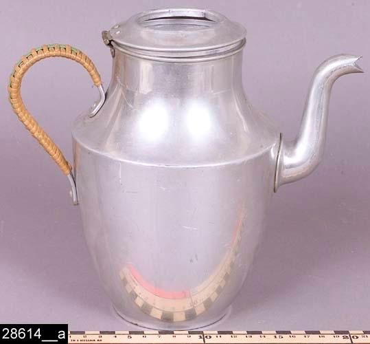 """Anmärkningar: Kaffebryggare, 1930-tal.  Kärlformad kaffebryggare med lock, S-formad, kluven pip och ett handtag isolerat med vidjor. Undertill är kaffebryggaren märkt med en krona samt texten """"SKULTUNA 1607 1 1/2L"""" (bild 28614__b). Tidsangivelsen grundar sig på att föremålet finns avbildat i kataloger från Skultuna under 1930-talet. I en katalog från 1931 framgår det att kaffebryggaren tillverkades i två olika storlekar och kostade 8,30 kronor (bild 28614__c). Enligt en broschyr, utgiven av museet 2007 och benämnd """"Skultunastämplar 1800-2000"""", började den typ av stämpel som finns på föremålet användas 1922. Den användes fortfarande år 2007. H:210 D:135 Br:235 (avser måttet diameter samt handtagets och pipens mått)  Tillstånd: Insats, glaslock samt löstallriksfot saknas (jämför bild 28614__c).  Historik: Gåva från SAPA AB, Division Service, 2002. Föremålet stod i ett skyddsrum på bruksområdet i Skultuna."""