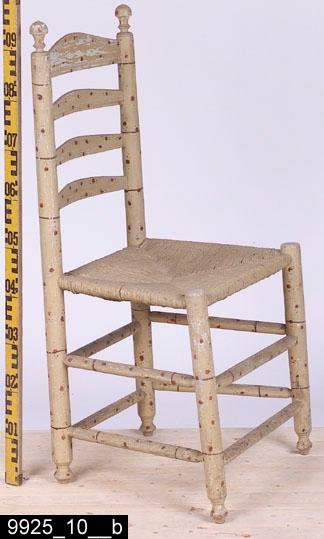 Anmärkningar: Stegstol, 1700-talets mitt eller senare hälft.  Överstycke med vågformad överkant och profilerad nederkant. Runda bakstolpar med svarvade dekorer längst upp. Genombruten rygg med tre ryggslåar som ser likadana ut som överstycket. Sits av flätad halm. Fyra runda ben med profilsvarvade fotavslutningar (bild 9925_10__b). Åtta benslåar förbinder benen. H:960 Br:485 Dj:410  Hela stolen är målad för att imitera bambu. Möblerna i serien 9925:1-12 söker imitera bambu. Sådana möbler har i omgångar varit populära i Sverige alltsedan kinasvärmeriet från mitten av 1700-talet till sekelskiftet 1800/1900. Enligt litteraturen på området tillverkades möblerna ofta för lusthus, en uppgift som också stöds av proveniensen från museets möbler - de har enligt liggaren stått i ett lusthus på herrgården Gideonsberg (riven på 1950-talet)!  Stegstolarna med invnr. 9925:7-12 (samt invnr. 28525) är inte tillverkade av Ephraim Ståhl. De är något äldre, förmodligen är de tillverkade runt 1700-talets mitt eller senast vid slutet av 1700-talet - åtminstone innan Ståhl blev mästare. Stegstolarna har målats samtidigt som, de av Ståhl tillverkade stolarna, d.v.s. omkring 1800. Stegstolarna har dock två lager av underliggande grå färg i olika nyanser av grått (även sitsen har varit gråmålad) som skymtar fram på flera ställen (bild 9925_10__c), vilket möblerna av Ståhl saknar. Troligen har den ursprunglige beställaren velat komplettera uppsättningen av Ståhlmöblerna och då tagit stolar som redan funnits på gården och låtit måla dem i samma stil som Ståhlmöblerna. Det råder ingen tvekan om att det bambuimiterande måleriet på stegstolarna och Ståhlmöblerna är utfört av två olika målare. För det första är måleriet mer klumpigt utfört på stegstolarna (vilket i sig pekar mot att en lokal gårds/bymålare utfört måleriet) än måleriet på Ståhlmöblerna som kännetecknas av tunnare och finare linjer. För det andra skiljer blandningen av färgen möblerna åt. Ståhlmöblernas färg är mycket intakt medan 