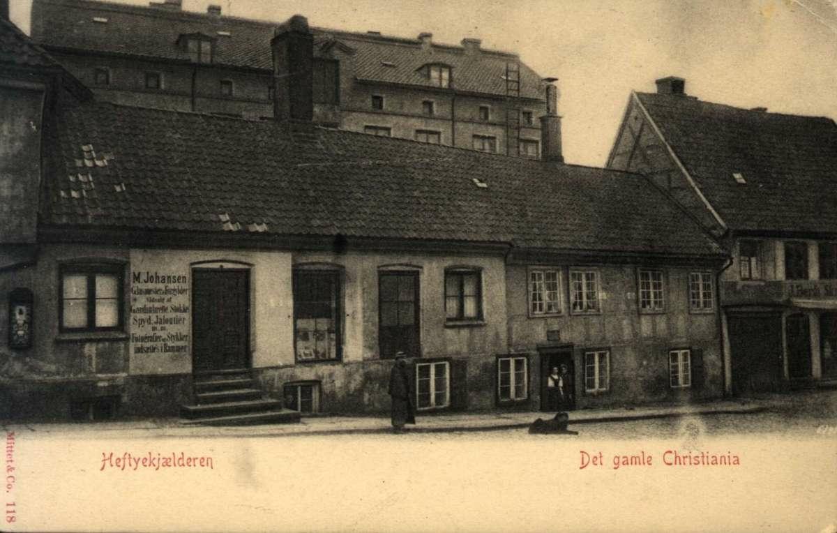 Postkort. Ubrukt. Fotografisk motiv. Svart/hvitt.  Fra det gamle Christiania: Heftyekjælderen (Storgata 2). Gate. Fotgjengere.