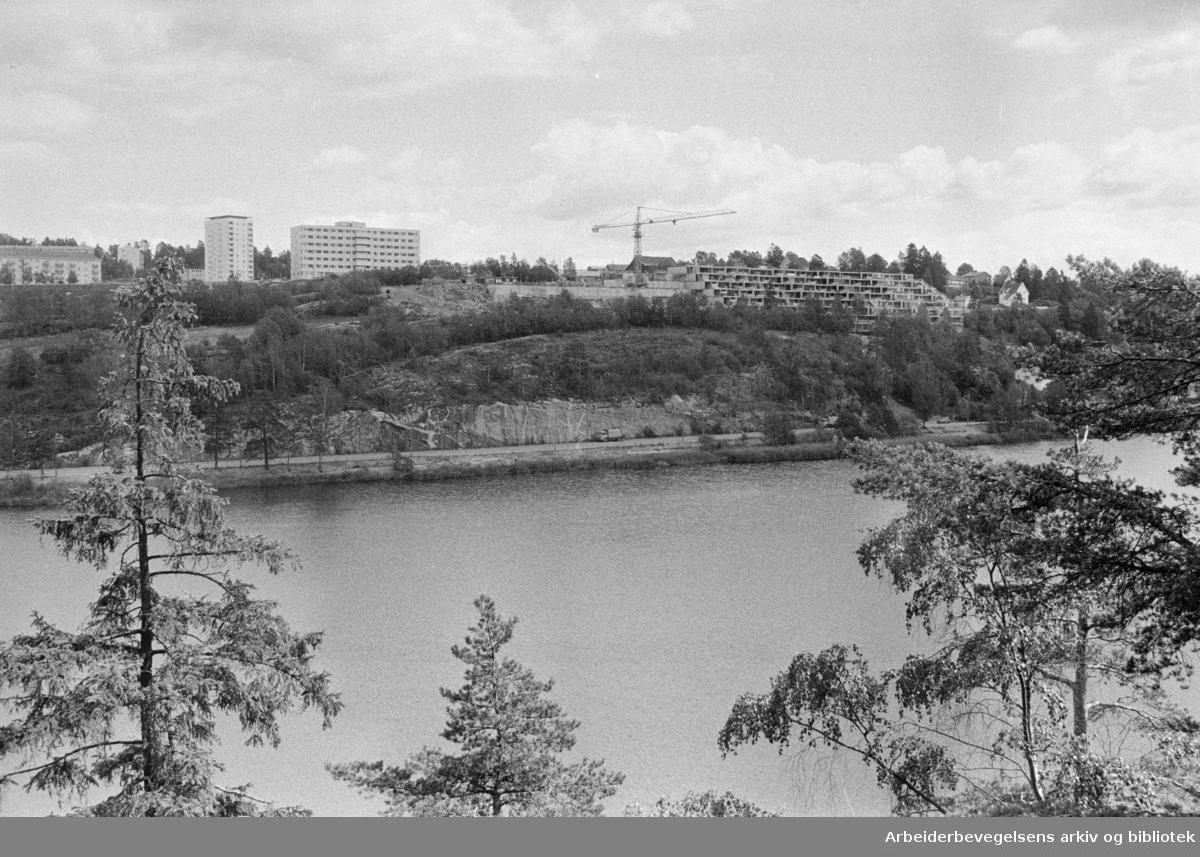 Oppsal. De nye terrassehusene ved Østensjøvannet under bygging. Til venstre, Oppsal pleiehjem som er tegnet av samme arkitekt, Torbjørn Rødahl. Juni 1976
