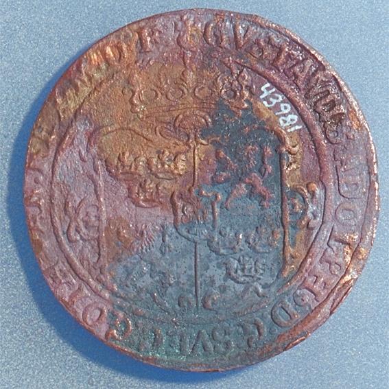 1 öre Runt mynt. Åtsidan: mitt på myntet det svenska riksvapnet, svagt och delvis synligt. Omskriften, med Gustav Adolfs titlar på latin, är svagt delvis synlig. till största delen oläslig. Ocentrerad prägling. Frånsidan: en örn framifrån med utbredda vingar, svagt  delvis synlig. Under örnen siffran 1 och versalerna ÖR, svagt  delvis synliga. Omskriften på latin, med bland annat präglingsåret 1628, är delvis läslig delvis oläslig, till största delen oläslig. Ocentrerad prägling. Nuvarande skick: bägge sidor slitna.  åtsidan sliten  frånsidan sliten.   jack  valsklump   korroderat   krackelerat Vikt: 24,0 gram.