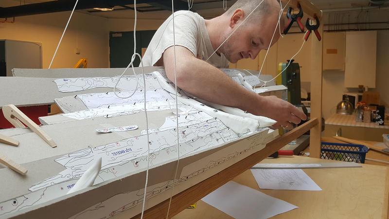 Arkeolog bøyer seg over og arbeider på innsiden av en uferdig båtmodell i plast og papp. Modellen er støttet opp i en treramme ved hjelp av klemmer og klyper i tre og plast, samt snører på flere steder. (Foto/Photo)