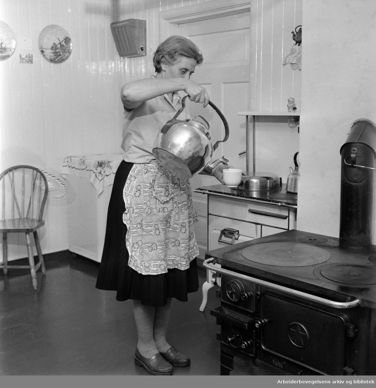 Nordmarka: Bonna gård. Lina Bonna skjenker kaffe fra en blankpusset kopperkjele. Desember 1960