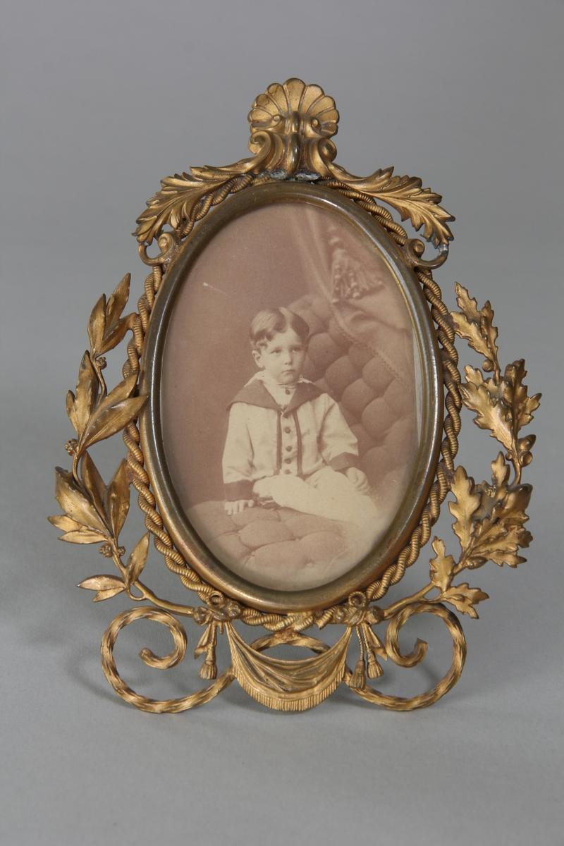 Fotografiram av gulmetall, oval med girlanger, lagerblad, ekblad, draperingar med mera. Stödben. I ramen fotografi av ung pojke, sittande i fotoateljé. Glasad.