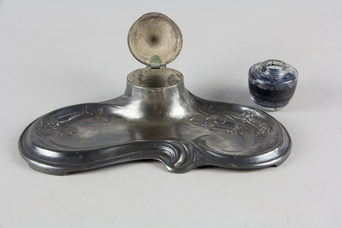 Skrivställ av britanniametall med sammanhållen bricka och bläckhorn i svepande jugendformer med dekor av blåsippor. Insats av glas med fällock av britanniametall.