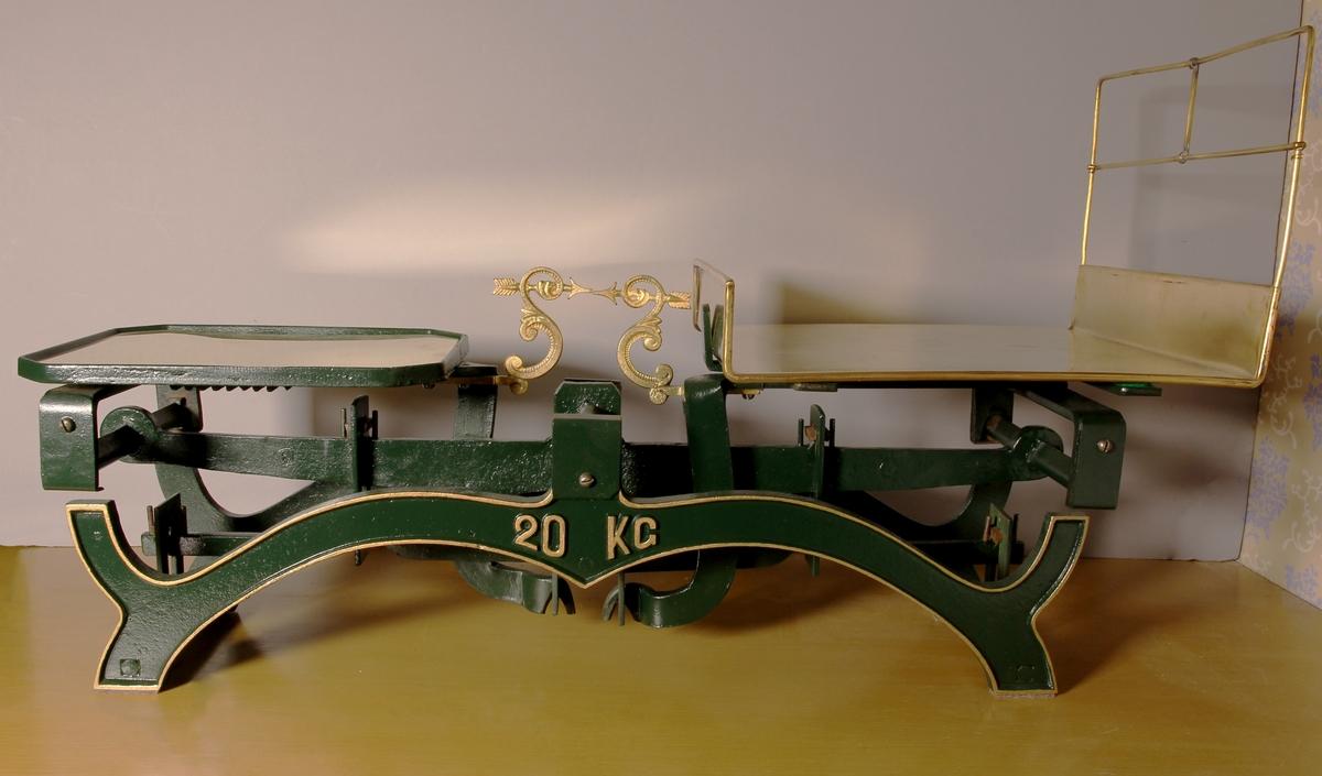 Våg, taffelvåg, av grönmålat gjutjärn och guldfärgade dekorationer. Avlång med två plana bord av mässingsplåt, det ena för vikter, det andra för det som ska vägas.