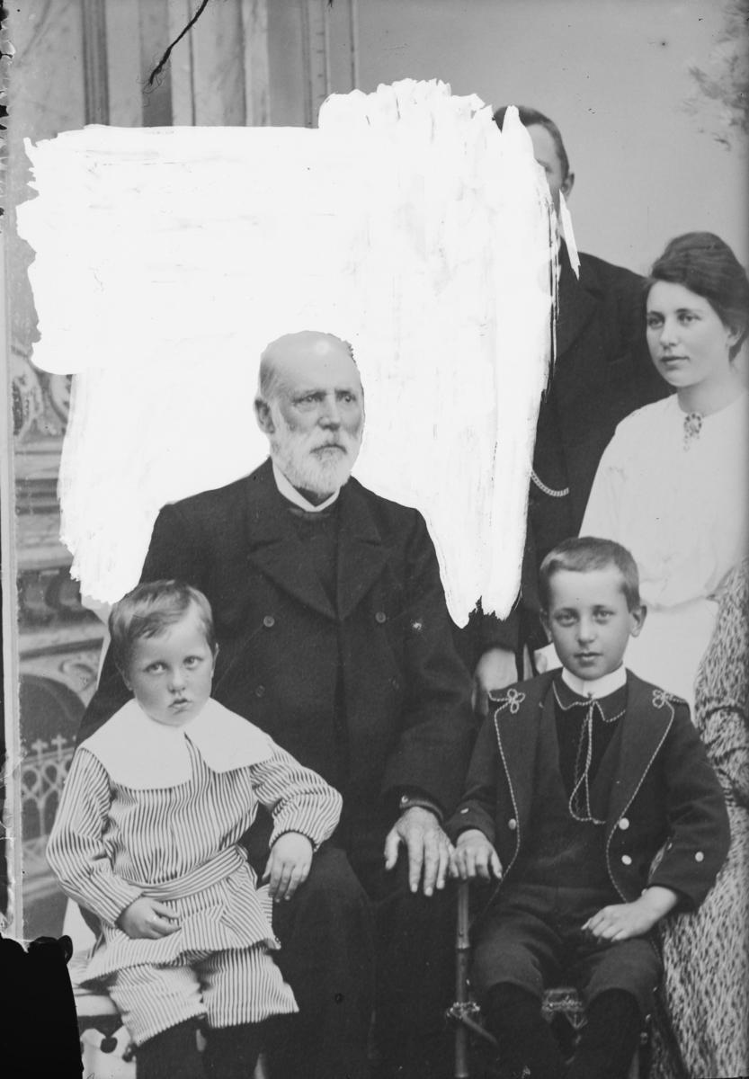 Portrett av ukjent mann med to barn - flere i bakgrunnen som er retusjert bort