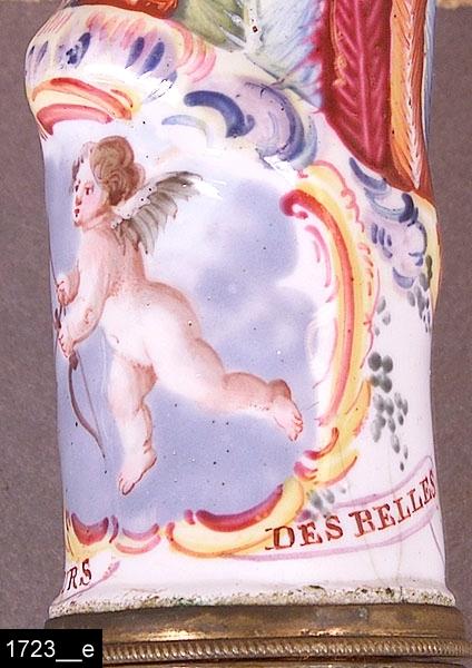"""Anmärkningar: Nålhus, rokoko/nyrokoko, 1700/1800-tal.  Fodral av läder med pressade dekorer, invändigt är fodralet försett med mönstrat papper (bild 1723__b). Nålhuset förefaller delvis vara av porslin och fajans. Den nedre delen är försedd med målade blommor (bild 1723__c). Den övre delen är försedd med en amorin med pil och båge som omramas av rokokoornament. Runtom figuren står det """"Pour les coeurs des belles"""" (ungefär """"för den ljuva kärleken""""), bild 1723__d-e. L:130 D:30  Historik: Gåva från änkefru Maria Lindgren, Västerås, omkring 1900."""