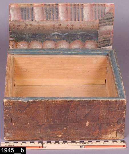 Anmärkningar: Timpask, omkring 1800.  Rektangulär timpask med skjutlock med avfasade kanter. Locket är kurbitsmålat och sidorna är brunmålade, all färg bär spår av naturligt slitage. Kanterna är profilerade. Invändigt är asken tom (bild 1945__b). H:125 L:290 Dj:270  Måleriet på föremålet är utfört av en dalmålare. Föremål med kurbitsmålning är kända långt utanför Dalarnas trakter. De har framför allt spridits till Gästrikland, Hälsingland, Uppland och Västmanland. Troligen har de sålts på marknader, både målade och omålade. Möjligen har dalfolket även sålt dem direkt i respektive landskap. Dalfolkets arbetsvandringar är väl belagda inom forskningen. Man vet också att dalmålarna kunde röra sig på mycket stora ytor, t.o.m. till Norge och Finland. Att de tog sig ned till Västmanland råder det ingen tvekan om.  Historik: Gåva från fru Sofia Fredriksson, N. Sylta, Munktorp sn, 1916.  Negativnummer: X-452