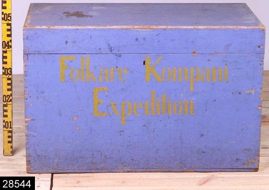 """Anmärkningar: Koffert, omkring 1900.  Gångjärnsförsett platt lock. Järnhandtag på kortsidorna. Invändigt är kofferten tom. Hela kistan är blåmålad. På framsidan finns påskriften """"Folkare Kompani / Expedition"""". H:525 L:820 Dj:435  Invnr. 28544 var tidigare märkt som invnr. 6528. Invnr. 6528 är dock en annan kista (och enligt liggaren består invnr. 6528 endast av en post) varför projektet Access under dess genomgång av bl.a. kistor 2007 försåg den här beskrivna kistan med invnr. 28544.  Tillstånd: Nyckel saknas.  Historik: Har tillhört Folkare kompani. Gåva från Kungliga Västmanlands Regemente."""