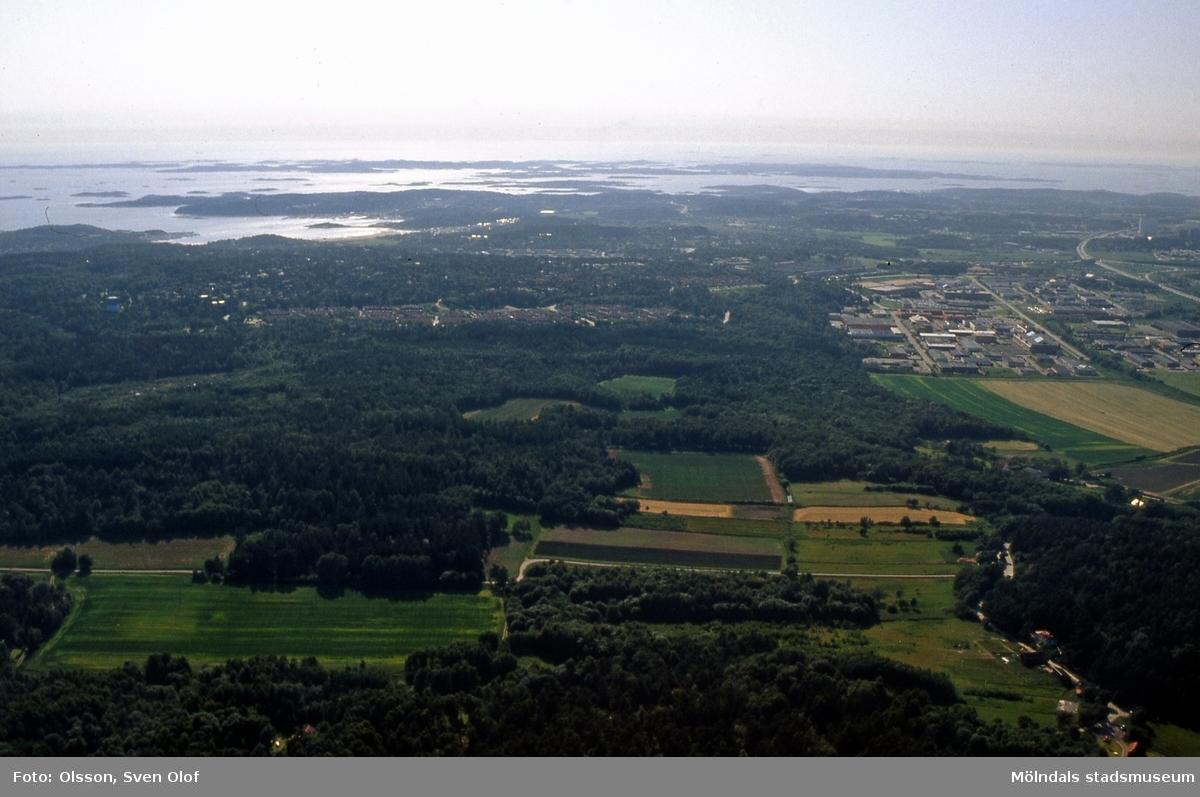 Flygfotografi över markerna i Balltorps berg, Mölndal, den 4/7 1991. Bortom det ses Sisjöns bostäder och industrier. FD 5:13.