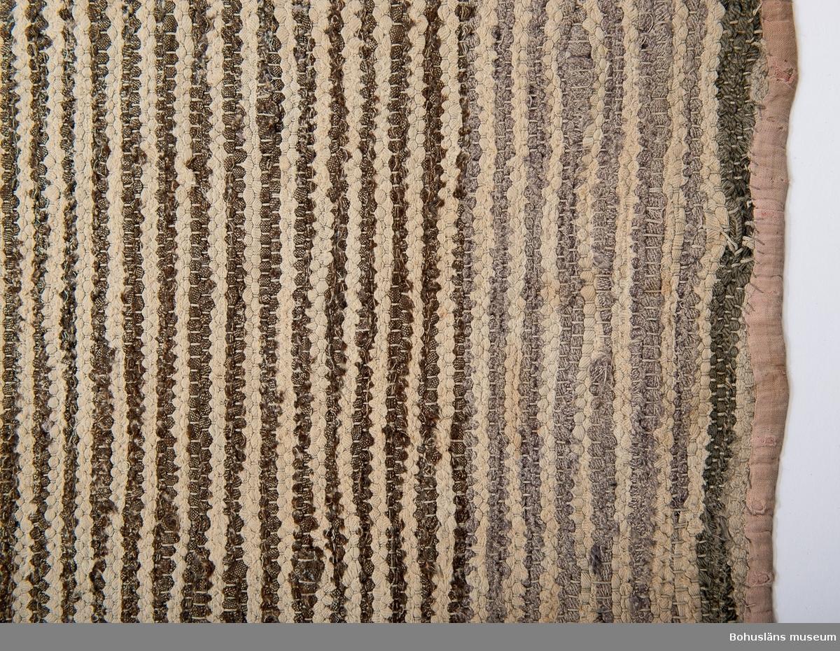 Tvärrandig. Cirka 40 cm breda smalrandiga partier med omväxlande två mörka och två ljusa inslag. Mellan de breda partierna finns ca 13 cm breda ljusa partier. Färger i de breda partierna: Blått, svart, olivgrönt, brunt omväxlande med ljusblått och grått. Färger i de ljusa partierna: Gulbeige, svagt rosa. Kortsidorna kantade med remsor av randigt bomullstyg, troligen rött med gula ränder från början. Blekt, smutsig, små hål här och var.  Ingår i föremålssamling ur sjöbod från Hällsö, Havstenssund, Tanum sn. Se UM017521