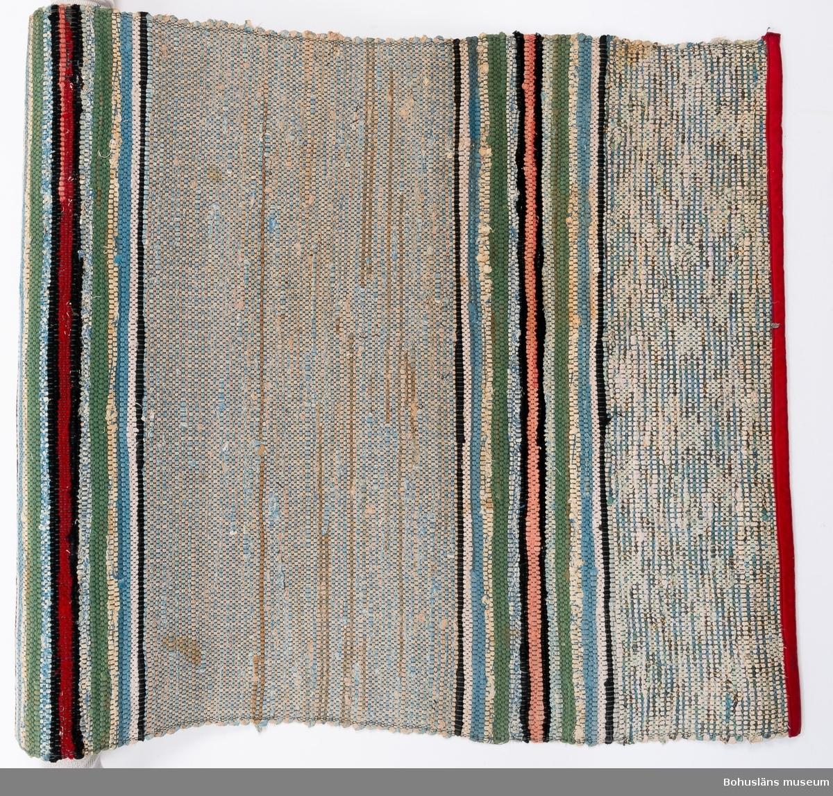594 Landskap BOHUSLÄN 394 Landskap BOHUSLÄN  Smalare partier med blått, grått, grönt, rött o.svart. Bredare partier därmellan i grått, blått, svart. Ändarna kantade med rött bomullstyg. UM21227:1-3 har likartad randning.  Litteratur: Kerstin Ankert/Ingrid Frankow, Den svenska trasmattan, en kulturhistoria,  Prisma 2003.  UMFF 3:2