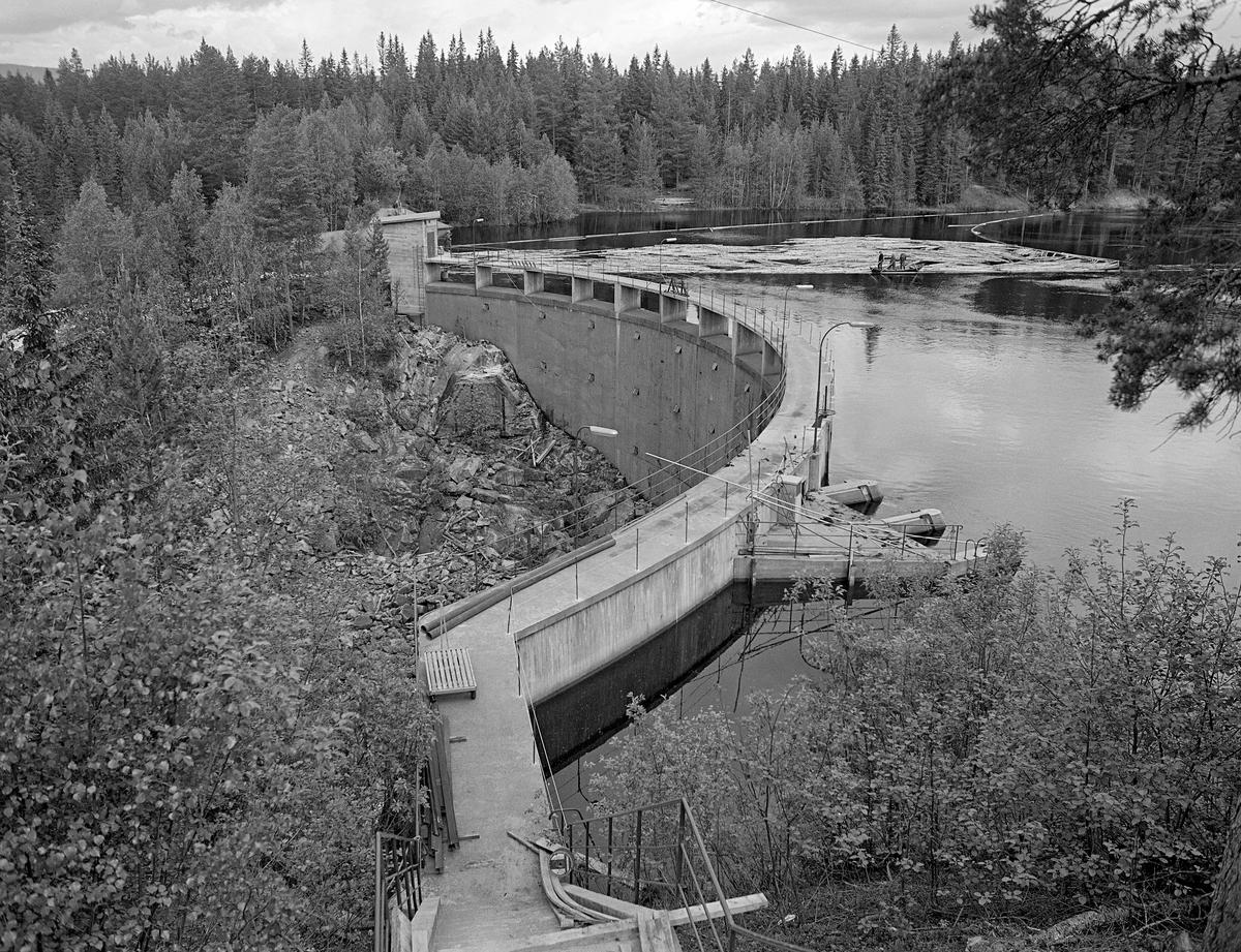 Sluttrensk på kraftverksdammen ved Osfallet i elva Søndre Osa i Åmot i Hedmark i mai 1984, den siste sesongen det foregikk tømmerfløting i denne delen av Glomma-vassdraget.  Fotografiet viser hvordan fløterne, fordelt på to robåter med ei mellomliggende lense, sørget for at løstømmer på vannspeilet ble trukket mot kraftverksdammen.  Der var det lagt ut lenser for å lede virket mot tømmerløpet som var plassert mot det nordre landet, hvor fallhøyden var mindre enn nedenfor den buete hoveddammen mot søndre landside.  Damanlegget på fotografiet skal ha vært ferdigstilt i 1947.  Den ble noe ombygd i 1981.  Ettersom vassdragslovgivinga påla dem som drev tømmerfløting å fjerne installasjoner i vann ved opphør av virksomheten, ble tømmerløpet ved Osfallsdammen revet umiddelbart etter at fløtinga på dette fotografiet var avviklet.  Energiproduksjonen ved denne lokaliteten foregår i en kraftstasjonsbygning fra 1914, cirka en kilometer nedenfor den avbildete dammen, hvor det er installert to francisturbiner som kan yte 5.5 megawatt.  Den opprinnelige dammen ble ødelagt ved et dambrudd i 1916.  Det nåværende kraftverket utnytter et fall på 41 meter i elva Søndre Osa.  Vegen på sørsida av vassdraget fører ned til kraftstasjonen og derfra mot Fylkesveg 215 ved Oset.