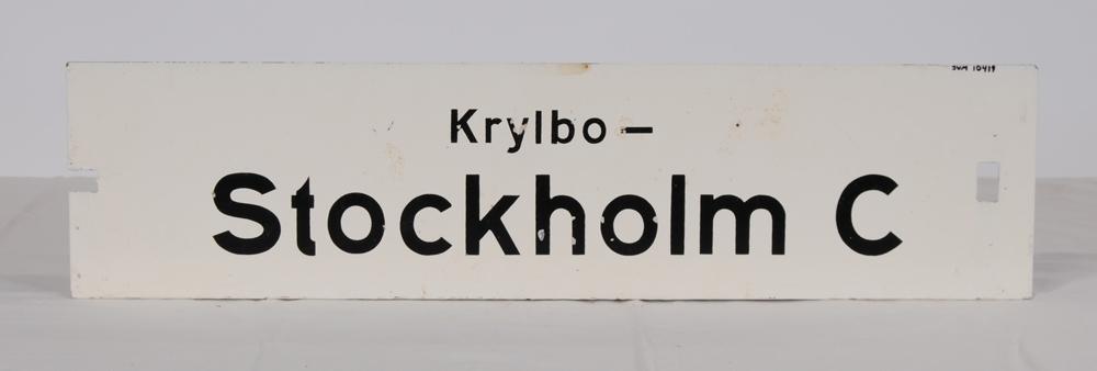 """Destinationsskylt av plåt med vitmålad botten och svart schablonmålad text. På ena sidan står det: Stockholm C-Krylbo, på andra sidan: Krylbo-Stockholm C. Slutdestinationen har större text. På den sida som det står """"Stockholm C-Krylbo"""" står det även """"Ky"""" uppochnedvänt i överkanten. I ena ändan av skylten finns ett rektangulärt jack och i andra änden ett rektangulärt hål."""