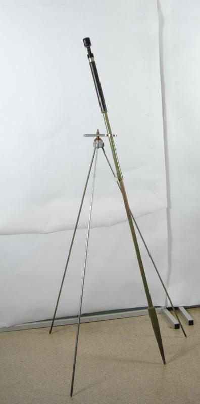 Stagstöd med tre ben med en hållare för käppen (Jvm 50384:1) längst upp och två vingmuttrar på en skruv som reglerar hållarens position. Obs! Måtten anges föremålets mått utfällt, men kan fällas ihop.