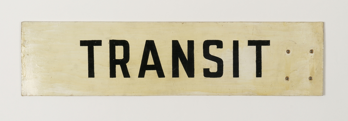 Rektangulært malt (og lakket på forsiden)  treskilt som angir info om transit. Fire hull i enden