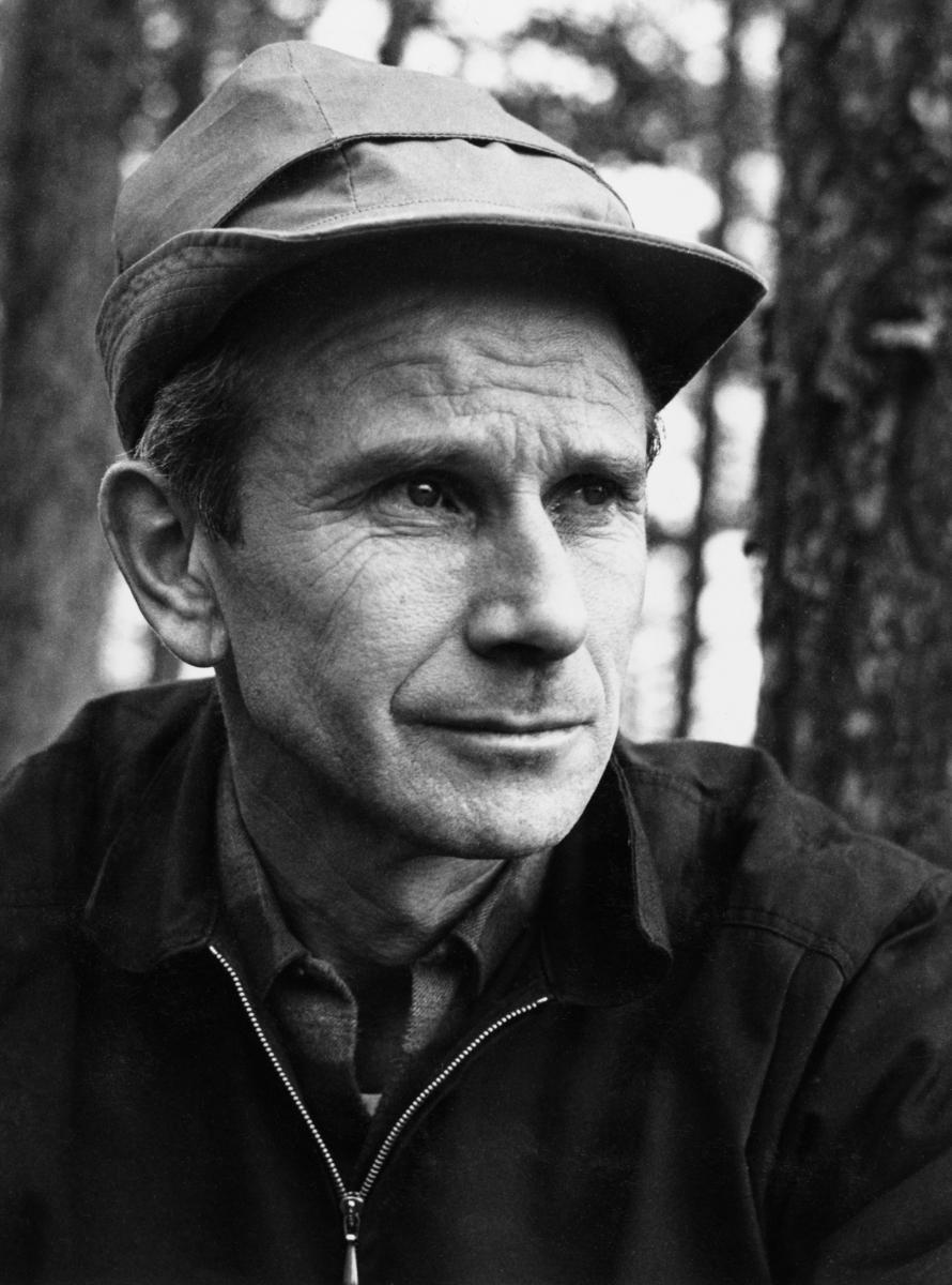 Portrett av elgjeger Knut Torp. Torp var utdannet forstkandidat (1954), og arbeidet først som skogsjef for firmaet And. H. Kiær & co., seinere for A/S Borregaard, som overtok Kiær-skogene i tillegg til de skogene Borregaard eide fra før.  Torp på denne måten ble Knut Torp fra 1963 skogsjef for arealer på bortimot en million mål fordelt på fire fylker, med Elverum som kontorsted.  Da dette fotografiet ble tatt var han cirka 46 år gammel.  Torp var kledd i rutete bomullsskjorte med anorakk over, og han hadde lue med skygge over pannepartiet.  Blikket er vendt noe til side for fotografen.  Bildet er tatt i glissen furuskog. Elgjakt. Storviltjakt. Jeger.  Mer informasjon om Knut Torp finnes under fanen «Andre opplysninger».
