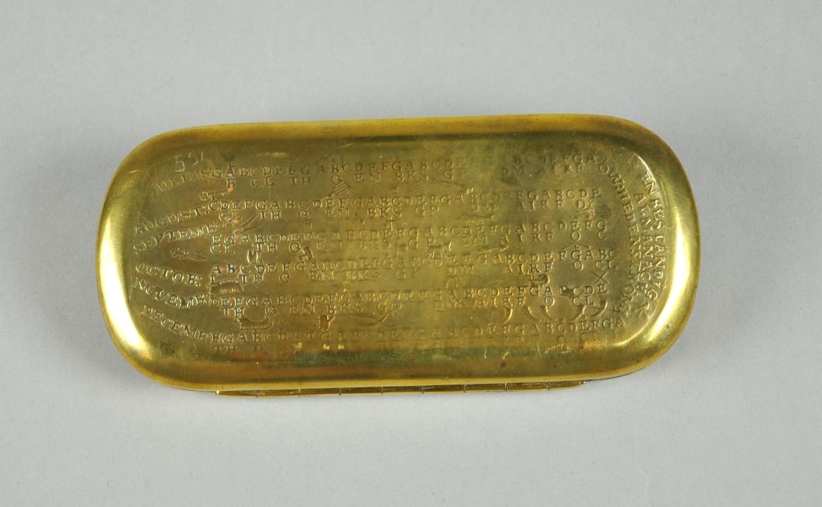 Dåse av messingmed lokk. Det er ingravert bokstaver i flere rader på lokket og på undersiden av dåsen. Dåsen har avrundede kanter.