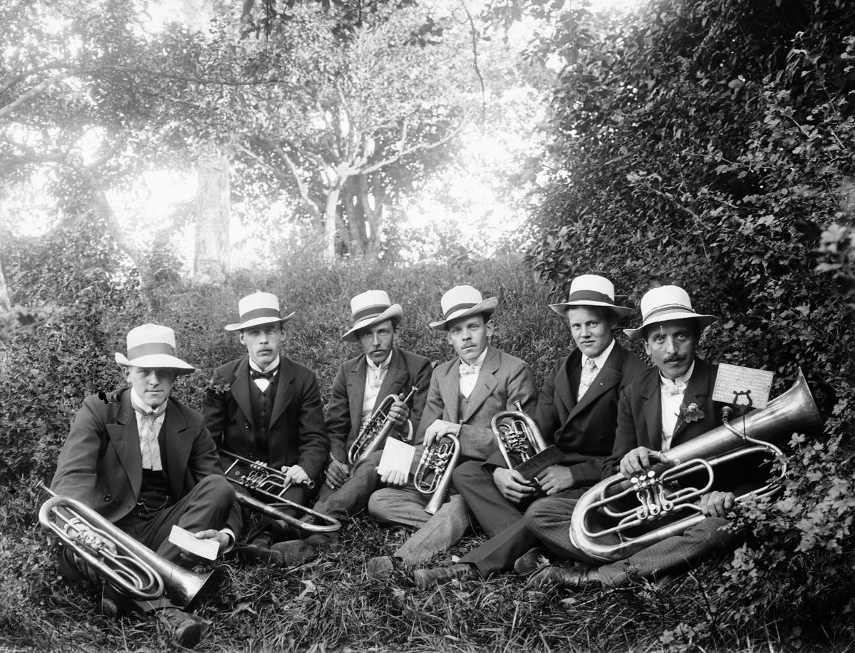 Män med blåsinstrument sitter i trädgård, sannolikt Sävasta, Altuna socken, Uppland