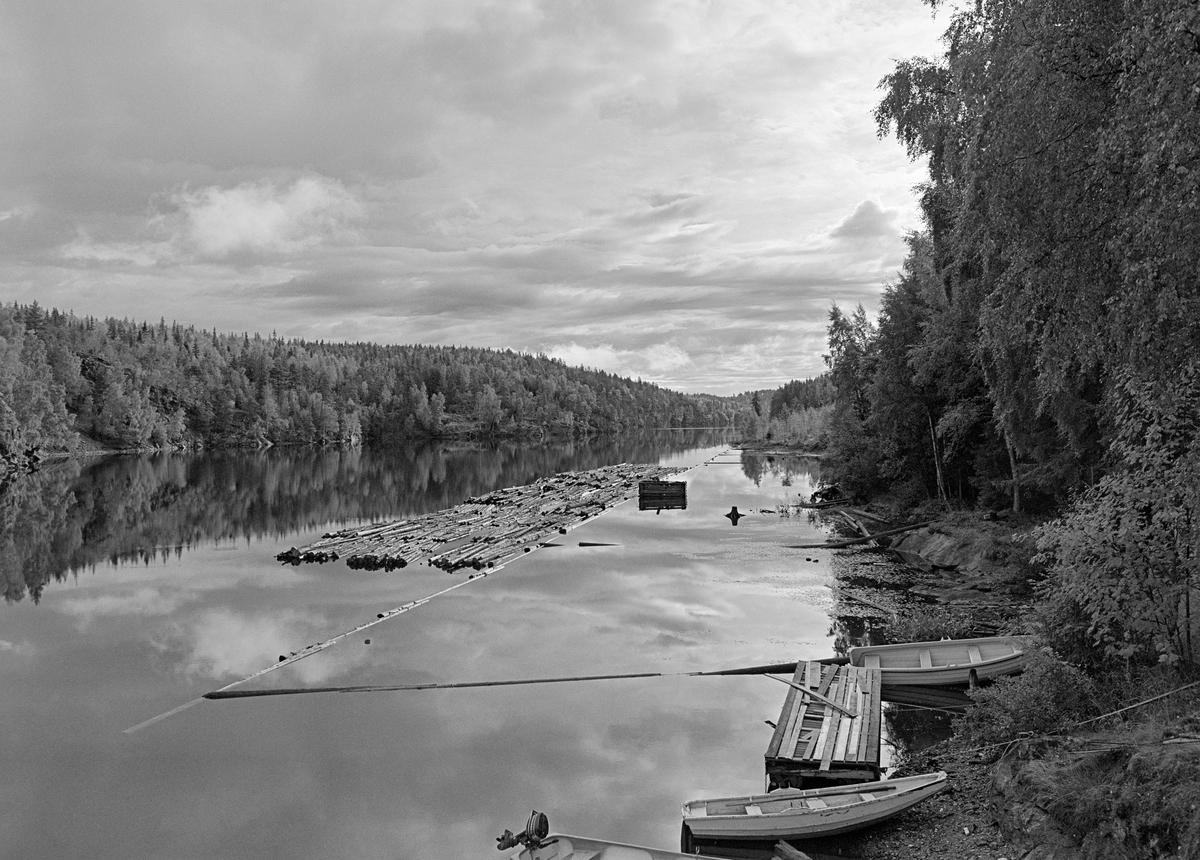 Fra dammen ved Brekke kraftverk i Stenselva i tidligere Berg herred i Østfold.  Fotografiet er tatt høsten 1982, som var den siste sesongen det ble fløtet tømmer i Haldenvassdraget.  Det viser hvordan buntet tømmer, som var slept fra Strømsfoss i Aremark, over Aremarksjøen, gjennom Tordivelen og over Aspern og gjennom de øvre delen av Stenselva, ble lagt langs ei lense på sørsida av dammen.  Her ble slepene oppdelt i kortere lenker som passet inn i slusekamrene.  De siste åra ble det utelukkende fløtet buntet, ubarket massevirke (papirråstoff) i tremeters lengder.  Av dette sortimentet gikk det fire bunter i hver slusevending.  Tømmeret ble til en viss grad trukket mot lensekanalen av et «drag» i vannet som lensinga skapte, men det fantes også et nokkespill til å trekke tømmerbunter med omtrent der fotografen sto da dette fotografiet ble tatt.  Dette er det tredje sluseanlegget som ble bygd ved Brekke.  Det første, som den kjente vassdragstekniske pioneren Engebret Soot (1786-1859) hadde idéen til, ble bygd i slutten av 1850-åra av stedlig stein med rosentorv som tettingsmateriale i murverket.  Dette sluseanlegget ble ødelagt under flom alt i 1861.  I perioden 1873-1877 bygde det statlige Kanalvesenet et nytt sluseanlegg ved Brekke, også dette med fire slusekamre, men åpenbart mer solid enn det første.  Fredrikshald (Halden) kommune sikret seg fallrettigheter ved Brekke alt i 1904.  Det varte imidlertid helt til 1918 før kraftutbyggingsprosjektet her ble påbegynt.  I åra som fulgte ble det bygd en massiv betongdam ved Brekkefossen som var 110 meter lang, og som på grunn av vanskelig grunnforhold måtte få en høyde på opptil 38 meter.  Kraftverksdammen hevet med andre ord vannspeilet i den ovenforliggende delen av Stenselva kraftig, slik at det ble nødvendig å bygge et helt nytt sluseanlegg.  Dette ble utført i armert betong, med stålporter og hydraulisk styring, og det ble tatt i bruk i 1924.  En liten historikk om tømmerfløting og kanaliseringsarbeid i Haldenvassdra